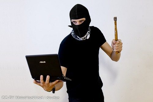 Image of hacker at work with hammer in hand