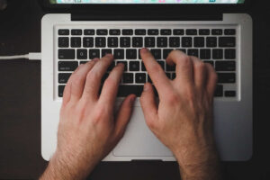 Image of man typing his business article on keyboard.